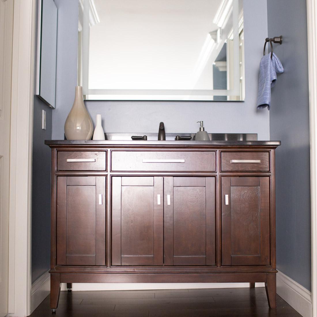 master bathroom vanity with dark stone top and backlit mirror in bedroom with grey blue walls design by sara bates interior design