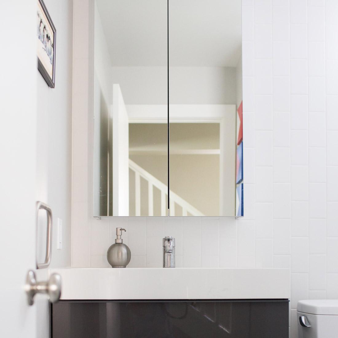 modern guest bathroom vanity with white vertical subway tile backsplash design by sara bates interior design