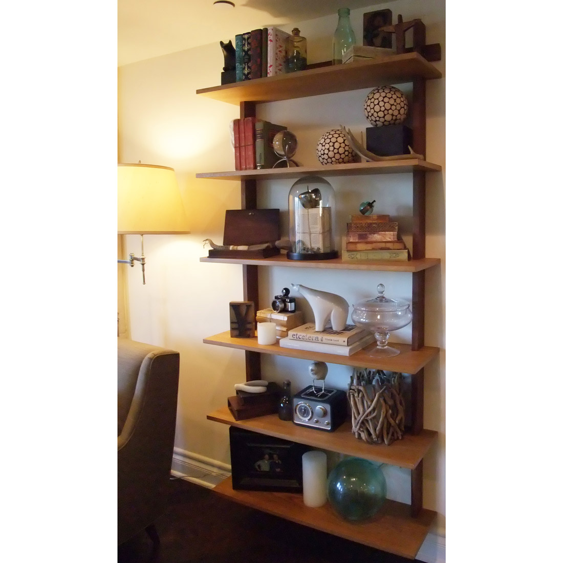 modern wood floating bookcase with accessories and display decor of curiosities design by sara bates interior design