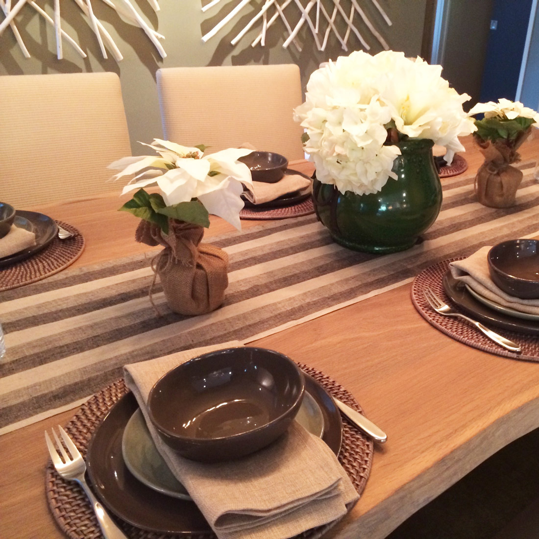 holiday table setting with stripe runner and white poinsettia centerpiece with rustic design by sara bates interior design