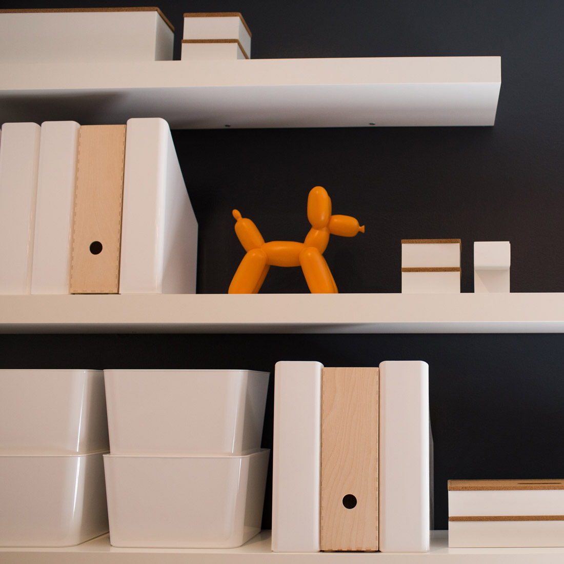 floating white shelves with white boxes and decor display items for an office space design by sara bates interior design