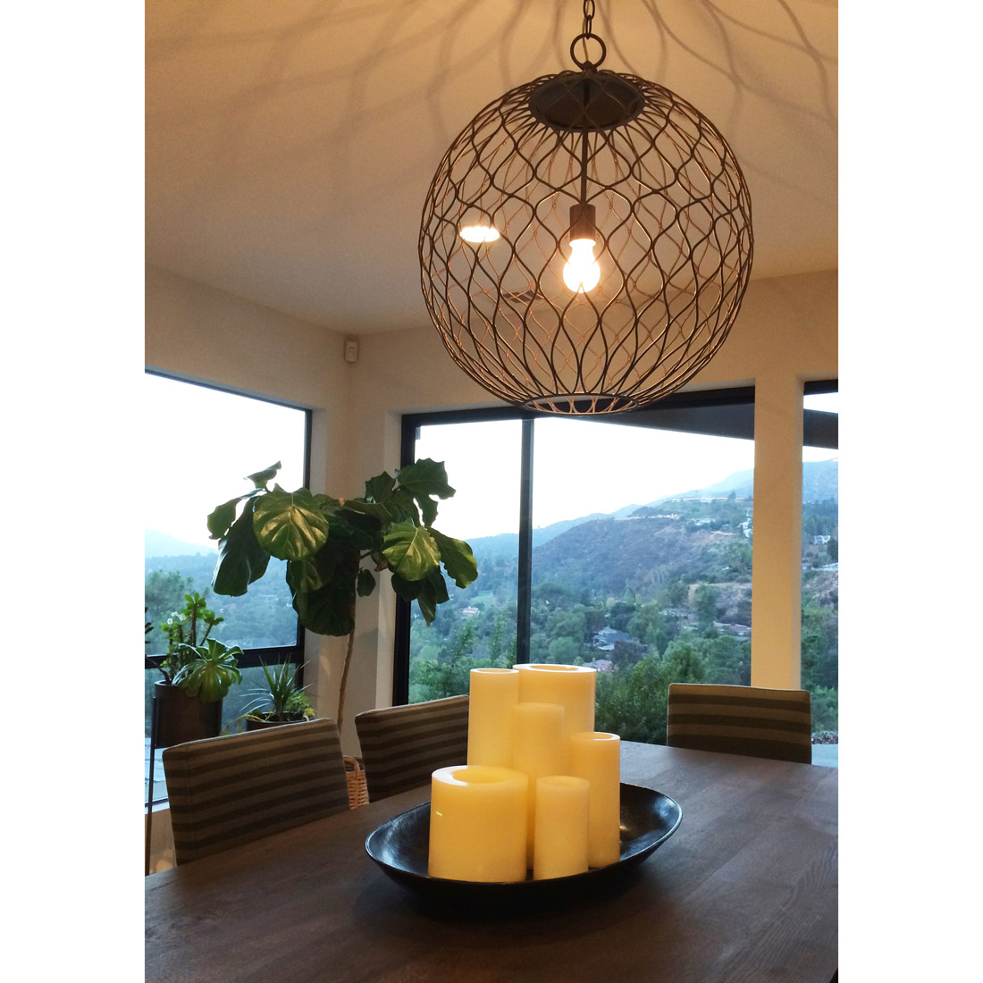 dining table with candle centerpiece and metal cage pendant light over looking the canyon and potted succulents and fiddle leaf fig design by sara bates interior design
