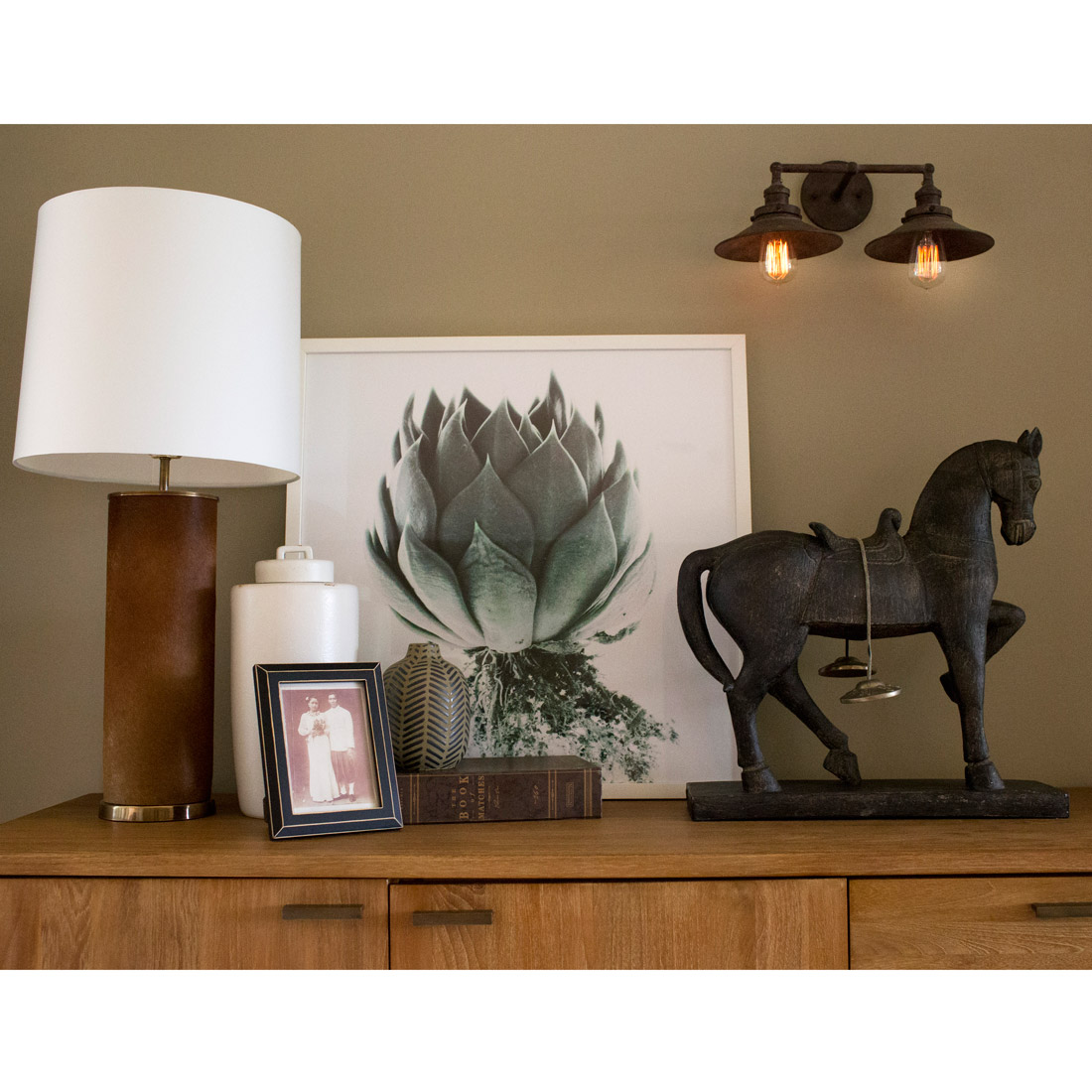 console table with decor items like a rustic sconce and horse figure with an artichoke photography art and cowhide lamp design by sara bates interior design