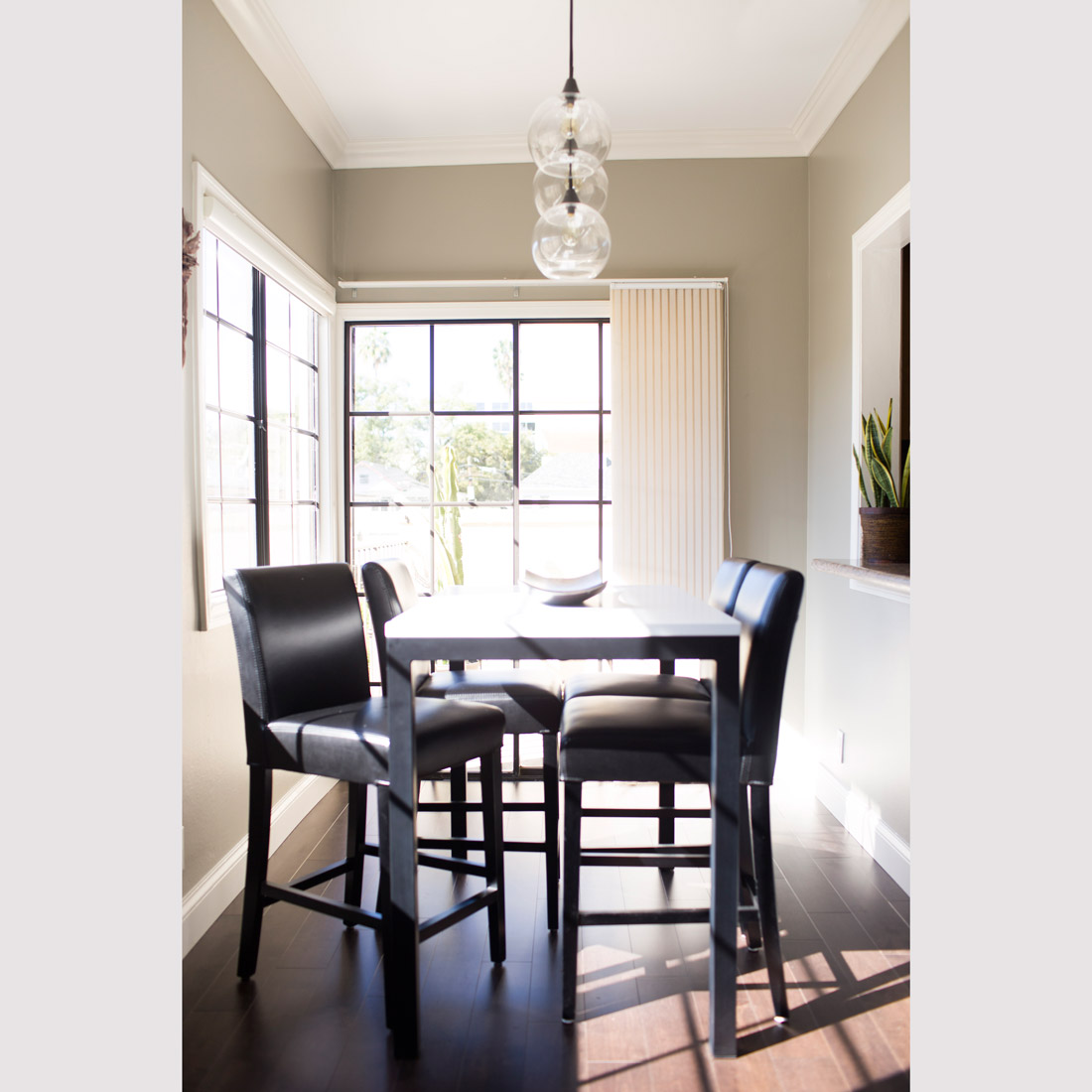 high dining table in white and black contrast and black leather counter height stools with globe pendant light and kitchen pass through design by sara bates interior design