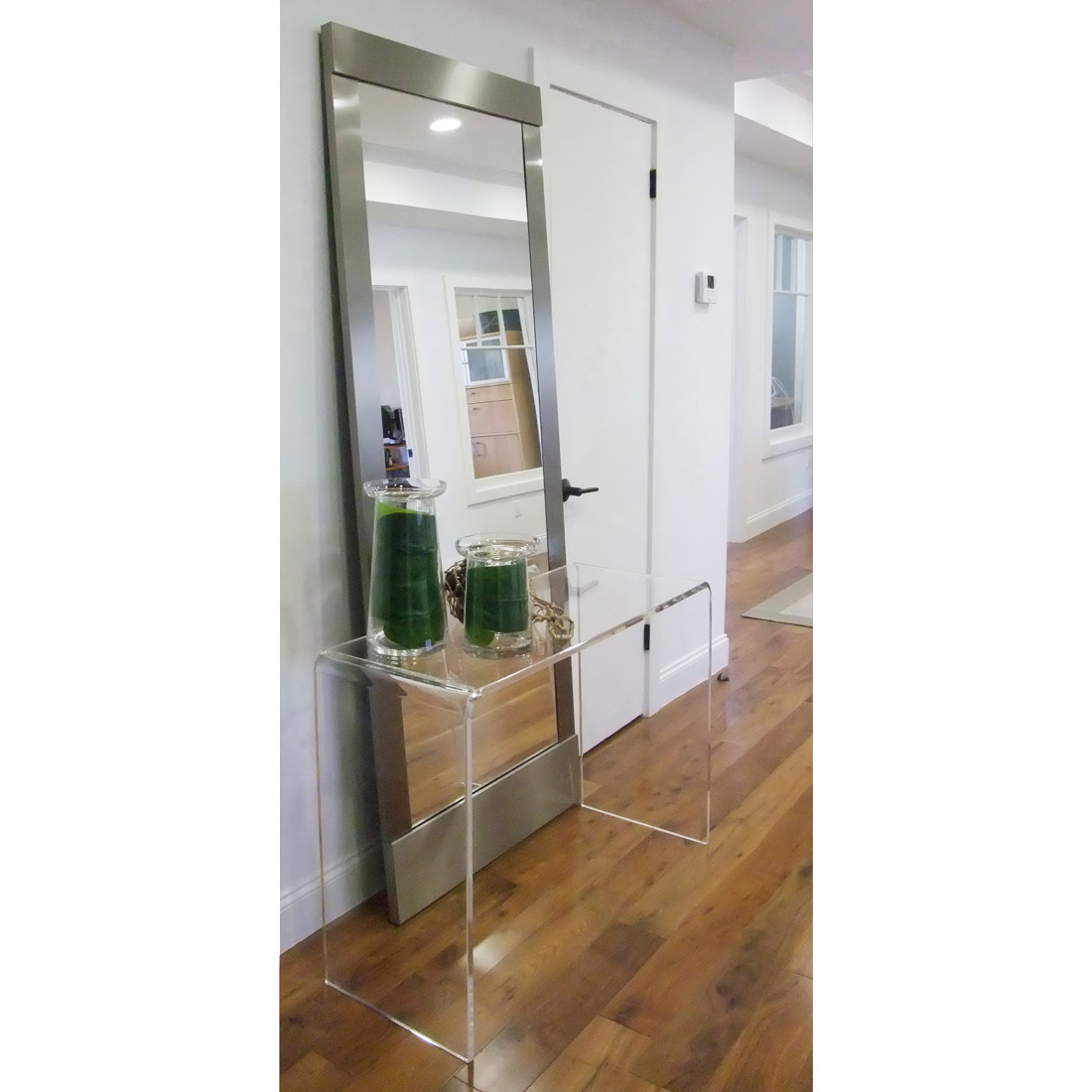 entryway with metal frame floor mirror and clear acrylic console table in office space design by sara bates interior design