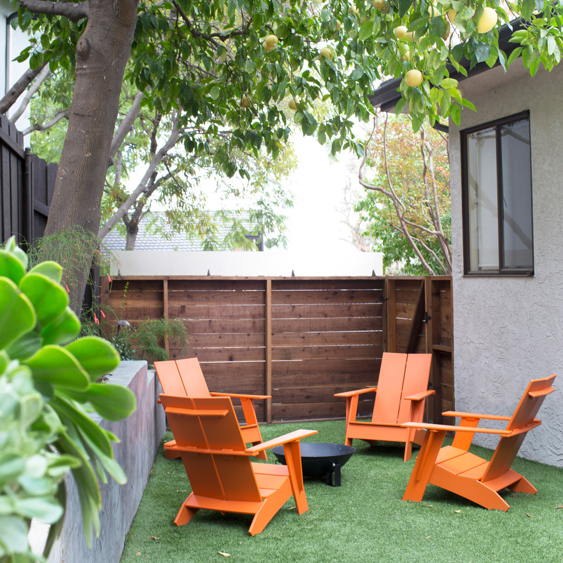 modern adirondack chairs around a fire bowl in a backyard grassy area orange plastic is easy to maintain with concrete retaining wall design by sara bates interior design