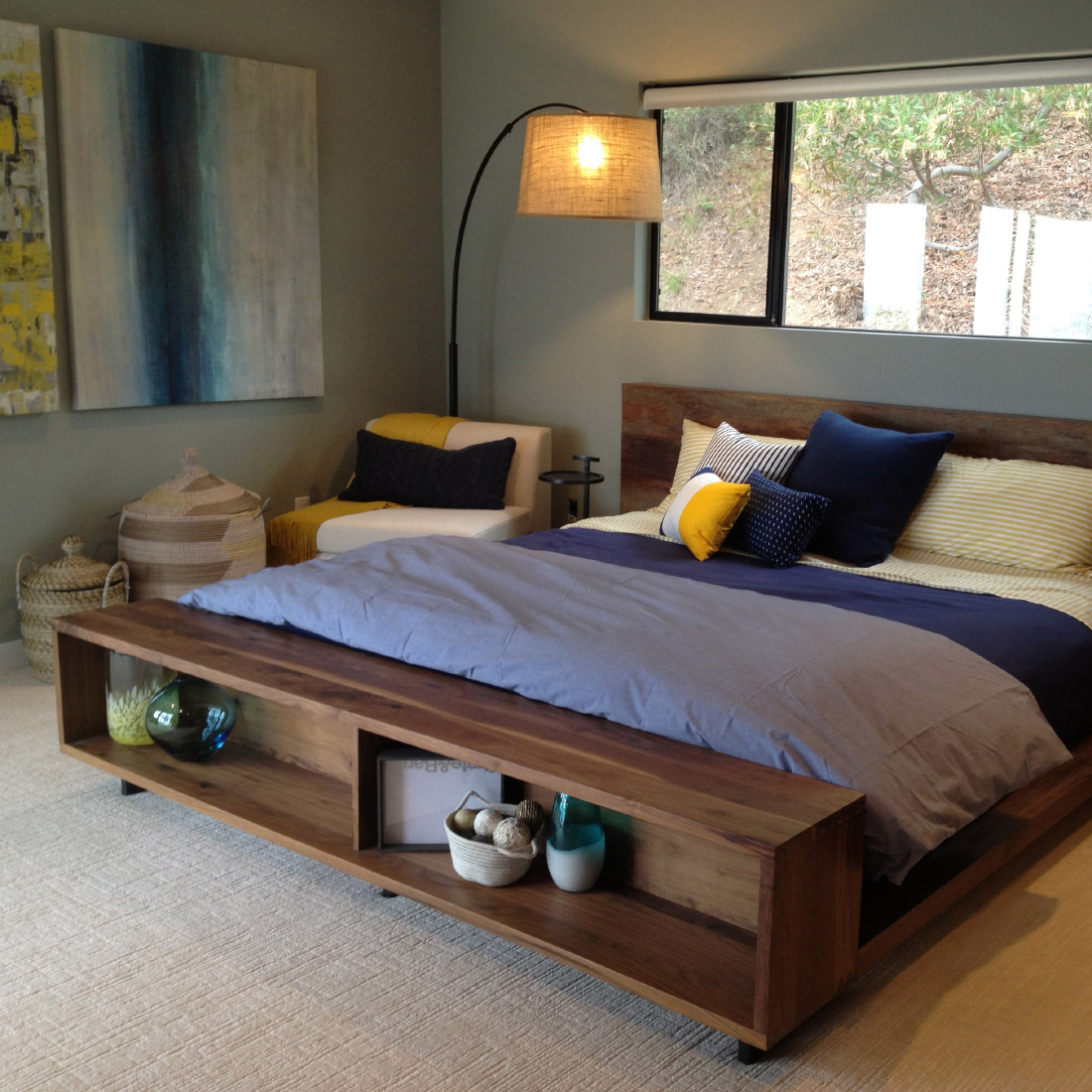master bedroom with reclaimed wood bed and arc lamp over an upholstered chair and modern large scale abstract wall art in blues and an accent of yellow design by sara bates interior design