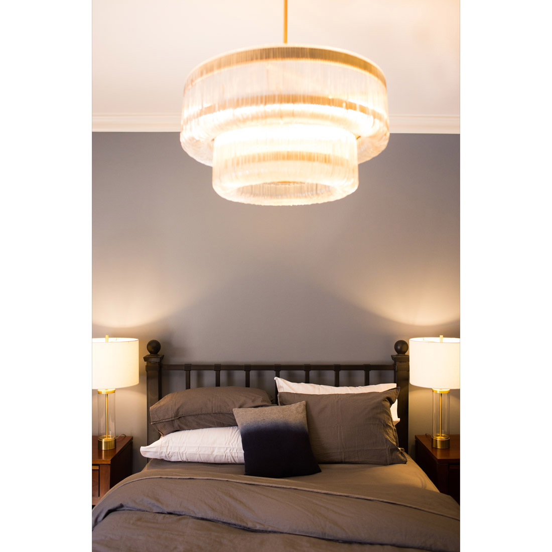 master bedroom with dark grey bedding and walls with hit of brass for sparkle with a gorgeous chandelier and glass column table lamps design by sara bates interior design
