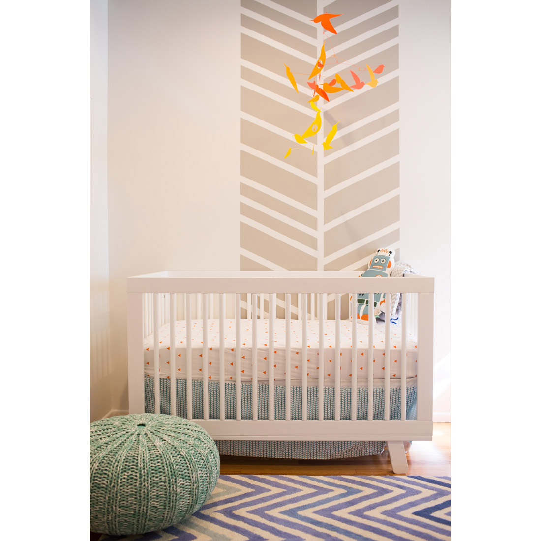 nursery white crib and orange bird moma mobile and chevron painted wall detail with teal pouf and blue zig zag rug design by sara bates interior design