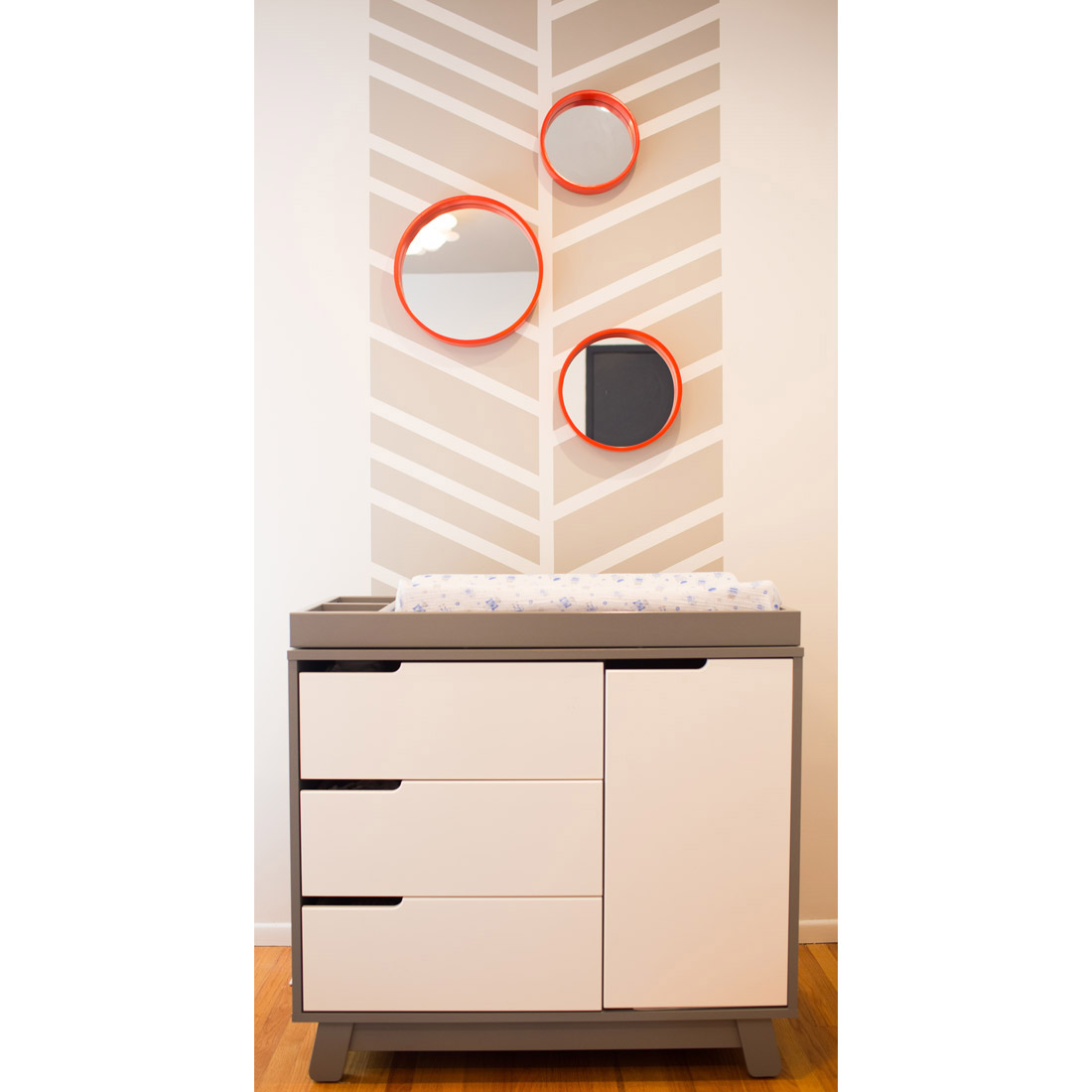 nursery changing table grey and white with painted chevron detail on wall and orange round mirrors for decor design by sara bates interior design