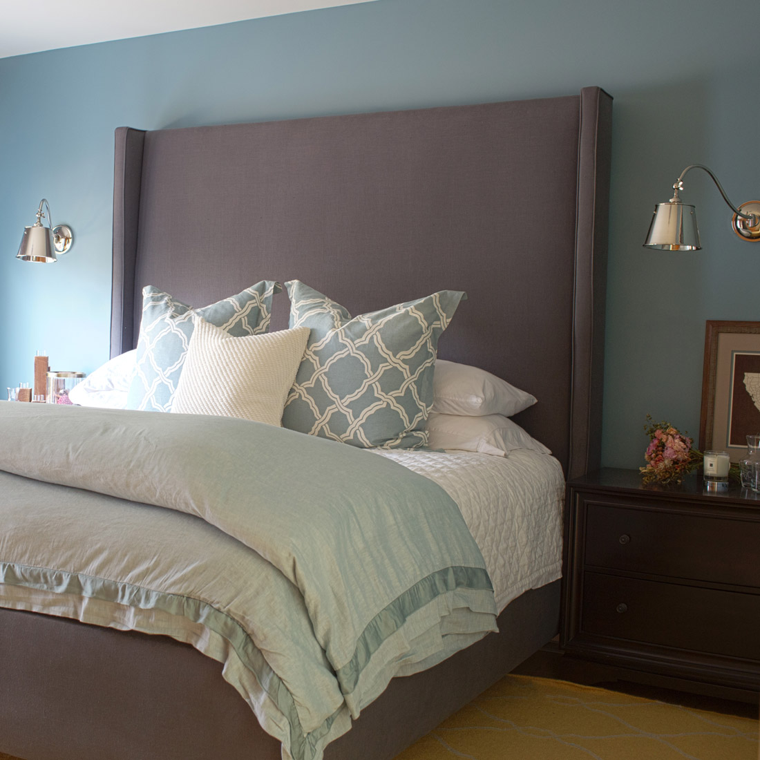 master bedroom with a serene linen bedding and dark wood side tables are accented by bright chrome sconces and a tall grey linen headboard custom made and design by sara bates interior design