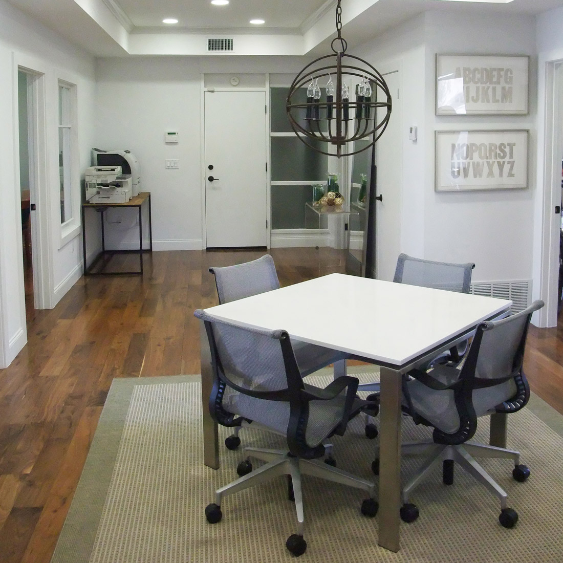 modern office with conference space white square table and pendant light design by sara bates interior design