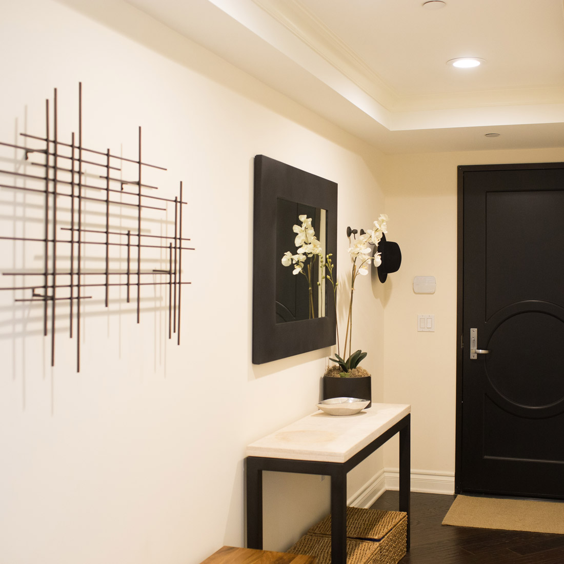 elegant entryway with geometric grey wallpaper modern accents and travertine top console with black metal legs and black metal framed mirror faux orchid with metal wall art and black painted front door woven baskets for storage and walnut entryway bench