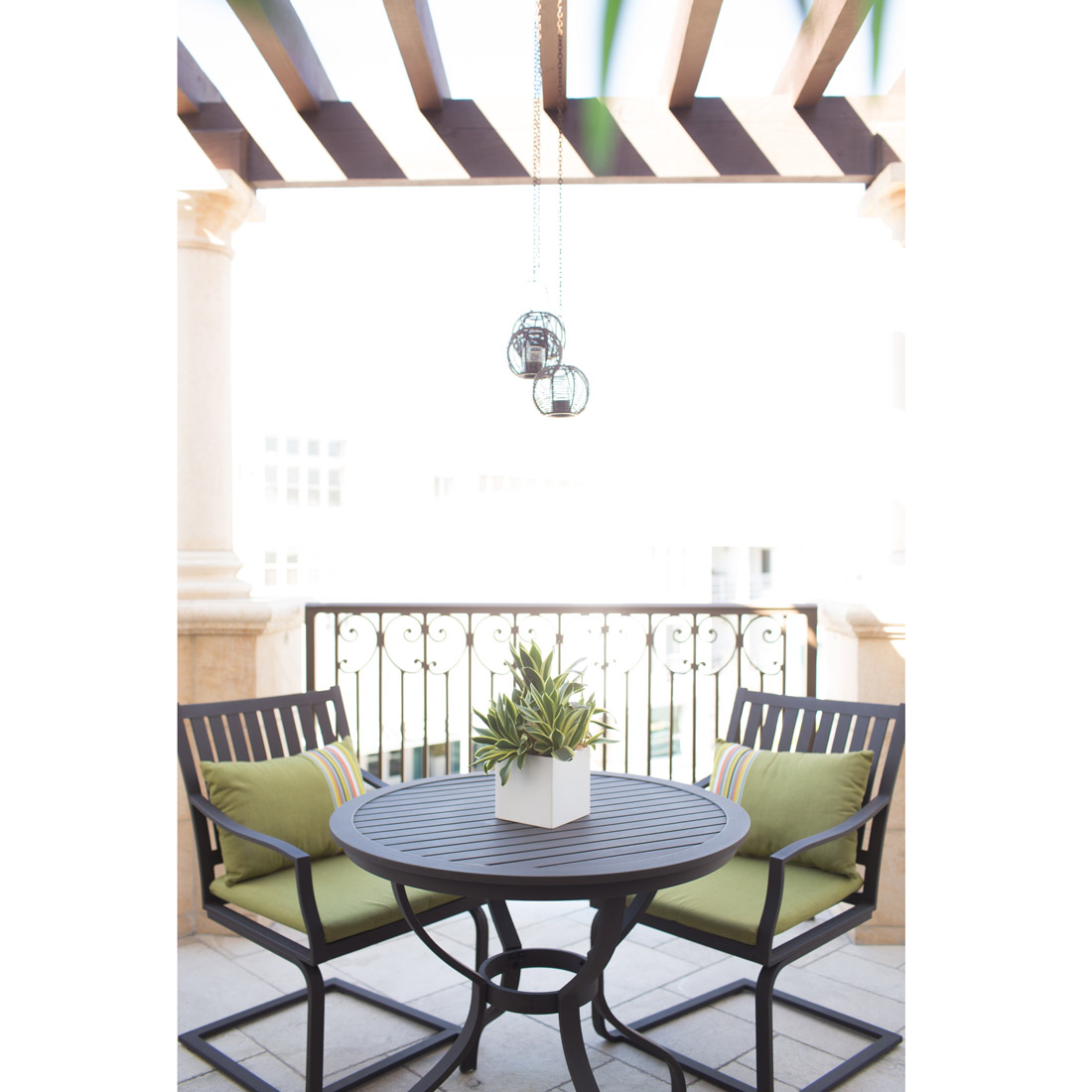 outdoor patio space with pergola and metal dining chairs and bistro table with green accents and sunbrella fabric cushions with succulent planter for centerpiece hanging metal globes with candles for outdoor lighting