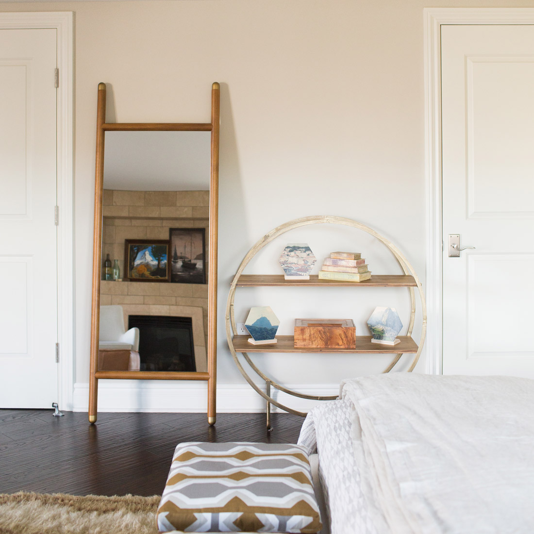 modern midcentury master bedroom with wood dowel and brass accent floor mirror and round metal frame with wood shelves bookcase accessories and geometric print on stool