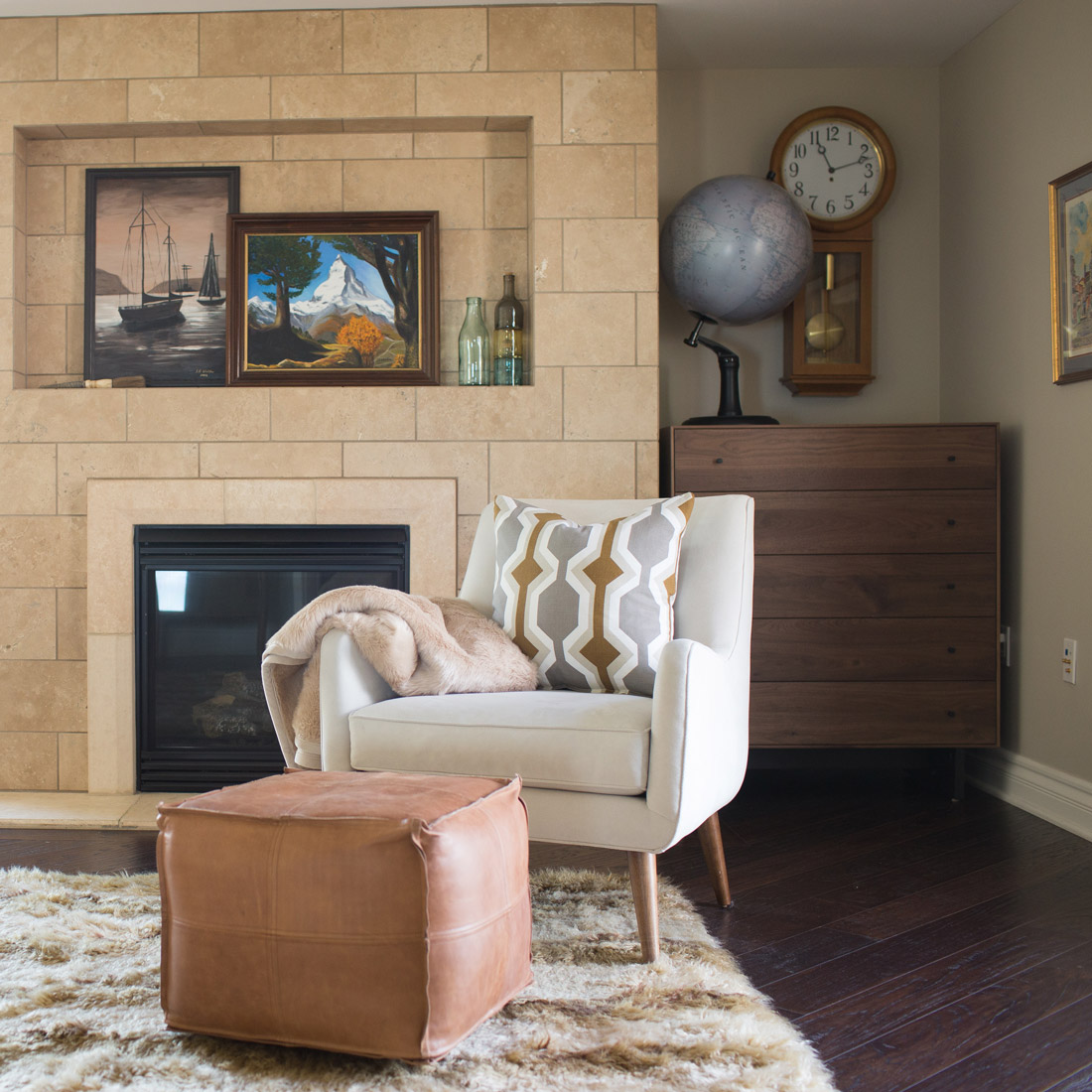 A modern midcentury seating area in a master bedroom in pasadena california modern white upholstered chair with leather ottoman and shag rug walnut dresser with client artwork and world globe accent the space with marble fireplace