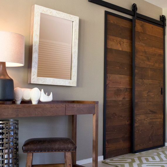 rustic wood barn doors with black metal accents and entryway console table in walnut wood with white bone chevron mirror jonathan adler rino object with black table lamp and leather stool