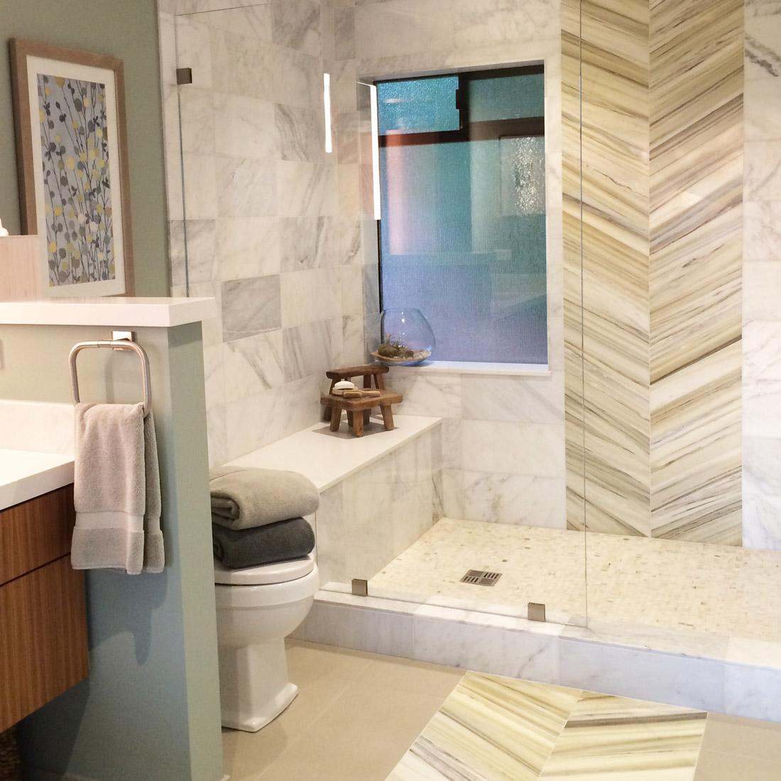 modern master bathroom shower with marble tile and bench seating with a rain head shower over a chevron tile pattern in wall and floor design by sara bates interior design