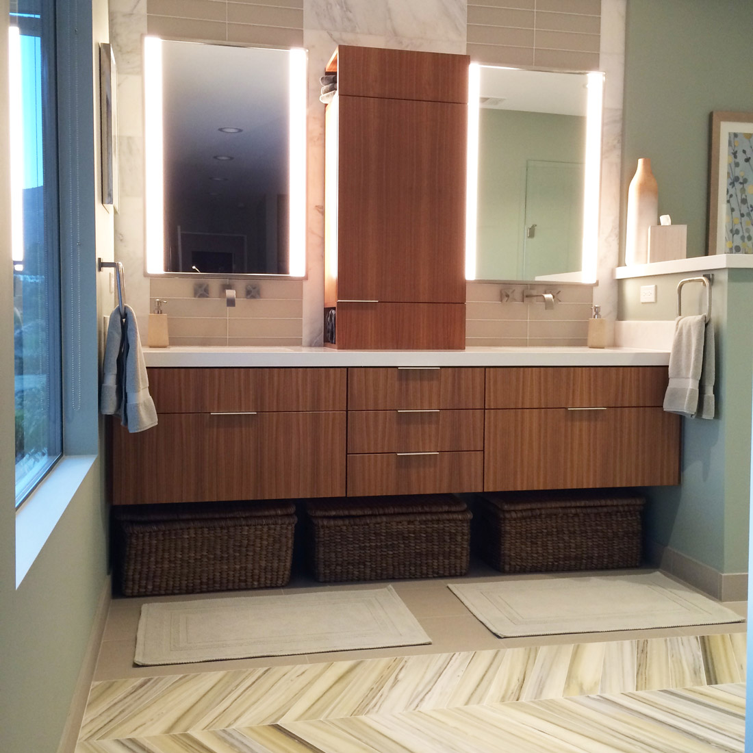 modern master bath with custom walnut floating vanity and glass and marble tile pattern for backsplash recessed lighted mirrors and chevron tile pattern on floor design by sara bates interior design