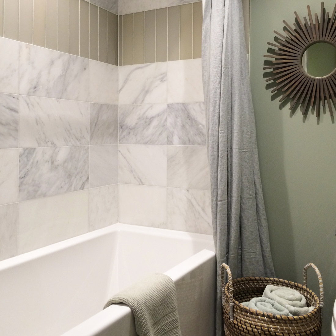 guest bathroom with marble and glass tile pattern in tub shower surround linen shower curtain and star burst mirror with basket for towels design by sara bates interior design