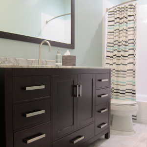 master bathroom with marble tile floors and vanity with dark stained wood and marble top spa like blue color design by sara bates interior design