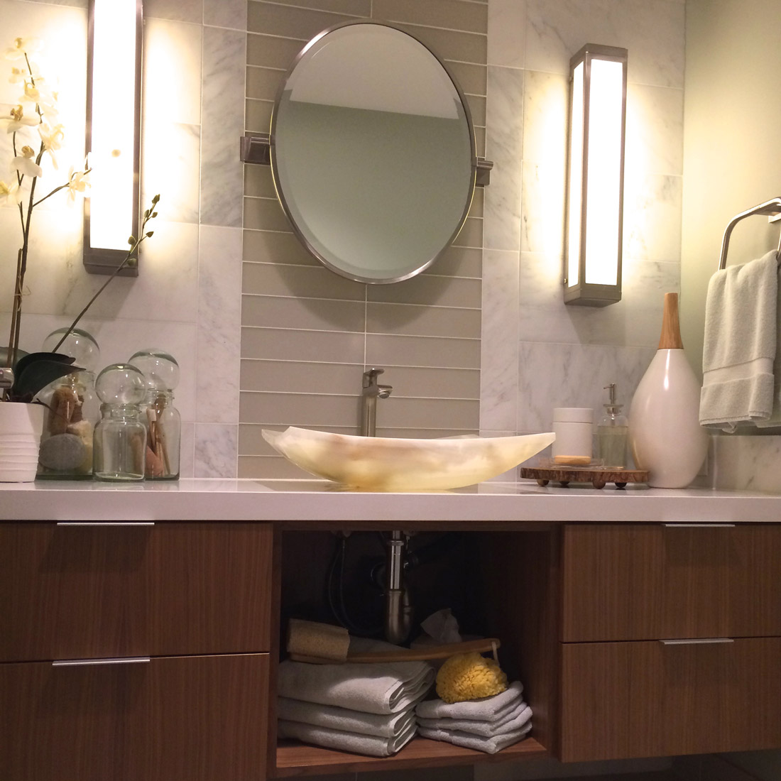 modern guest bathroom with glass tile detail and marble tile backsplash walnut floating vanity with onyx vessel sink and oval mirror design by sara bates interior design