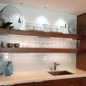 modern kitchen remodel with walnut open shelves and large format glass tile backsplash display glassware above barsink in ceasarstone white countertops design by sara bates interior design