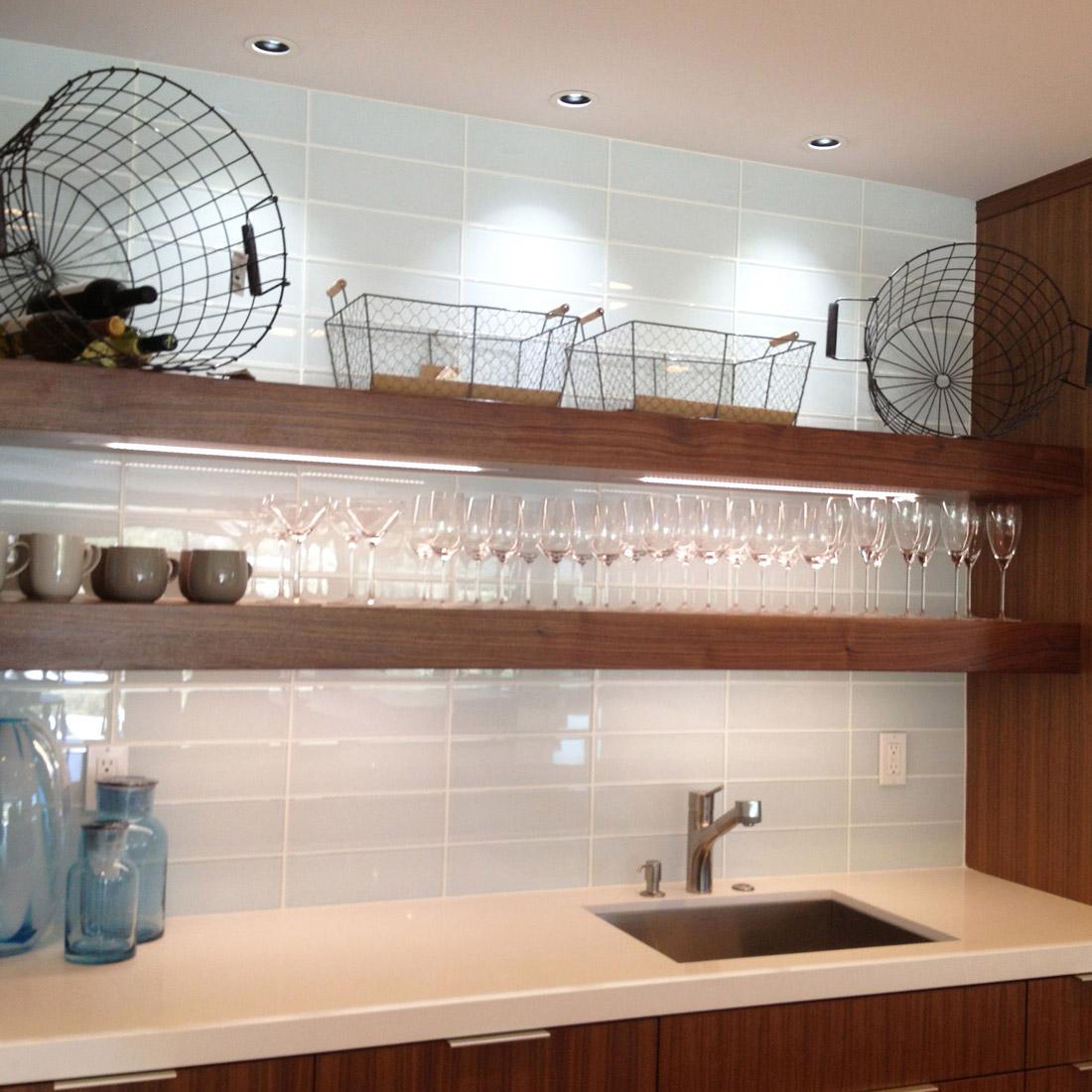 modern kitchen remodel with walnut open shelves and large format glass tile backsplash display glassware above barsink in ceasarstone white countertops design by sara bates interior design
