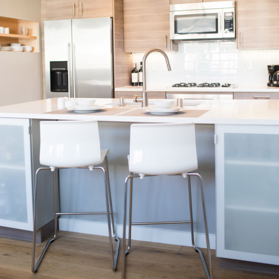 modern beachside kitchen remodel with grey cabinetry and frosted glass door fronts and white ceasarstone countertops with glass large format tile backsplash design by sara bates interior design