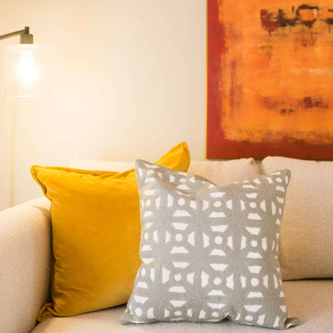 Pillow decor detail with yellow velvet pillow and grey crewel in contemporary geometric pattern on a neutral sofa bed and bright artwork design by sara bates interior design
