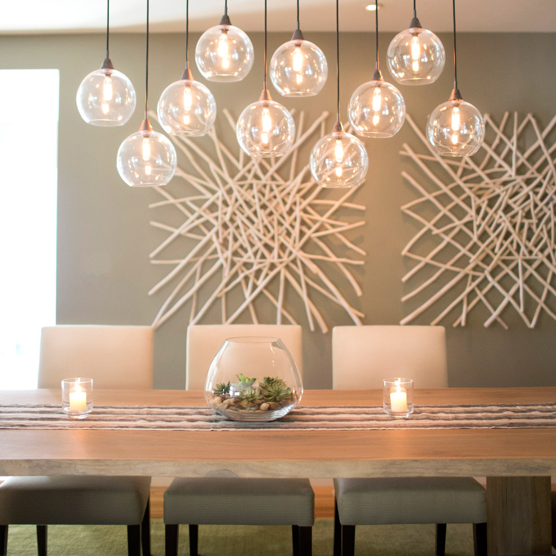 white oak dining table with live edge and succulent centerpiece hosts white upholstered dining chairs and globe pendant lighting with beach wood sticks wall art on grey green walls design by sara bates interior design