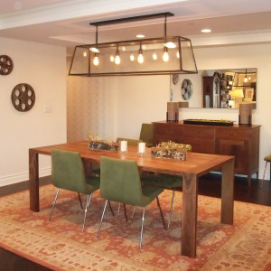 modern wood dining table with green upholstered metal leg dining chairs and glass pendant light with walnut wood sideboard and horizontal frameless mirror over a red pattern wool rug design by sara bates interior design