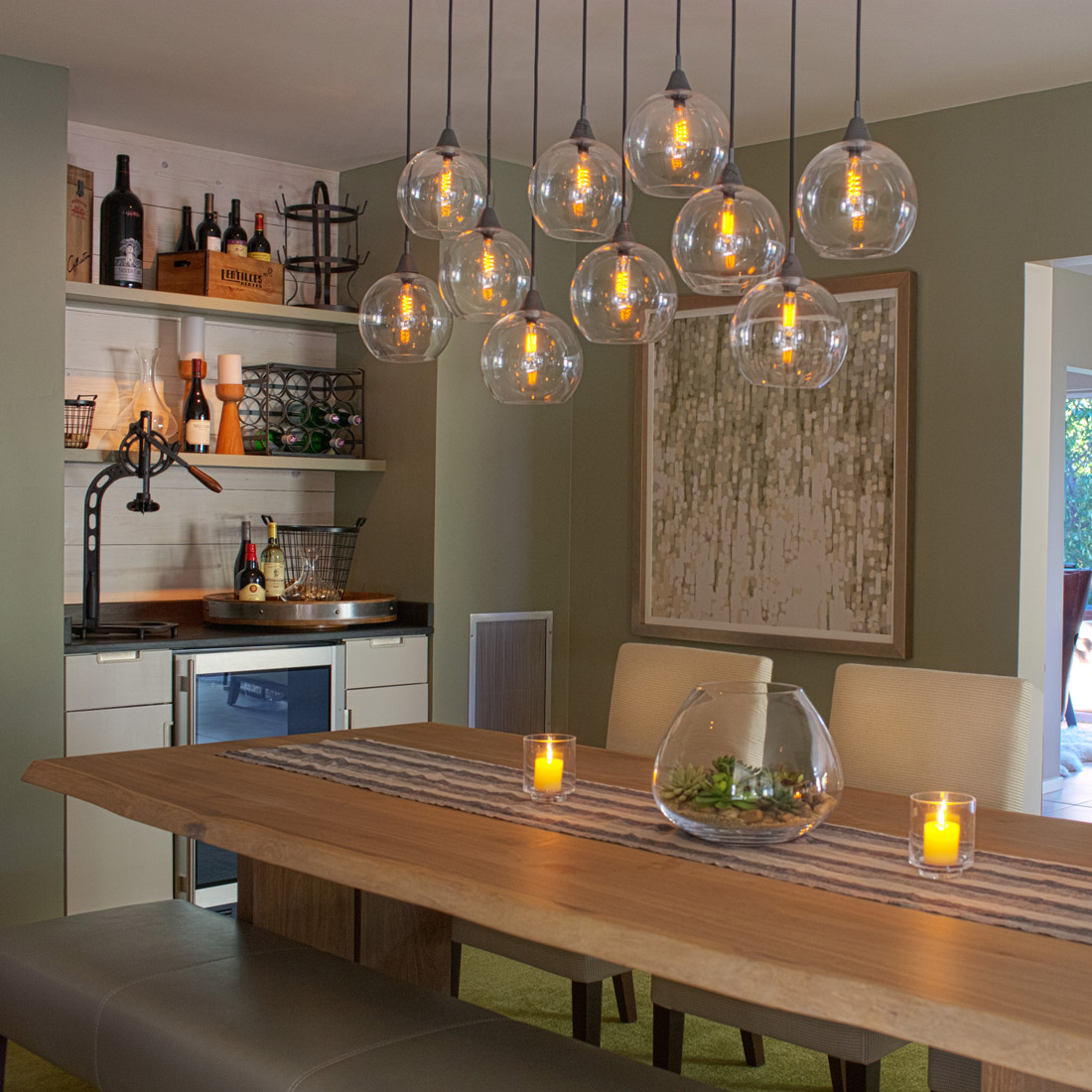 rustic modern dining room with globe pendants and bench seating mixed with white upholstered chairs and features a built in bar with wine fridge and wood cladding a grey green paint on walls design by sara bates interior design
