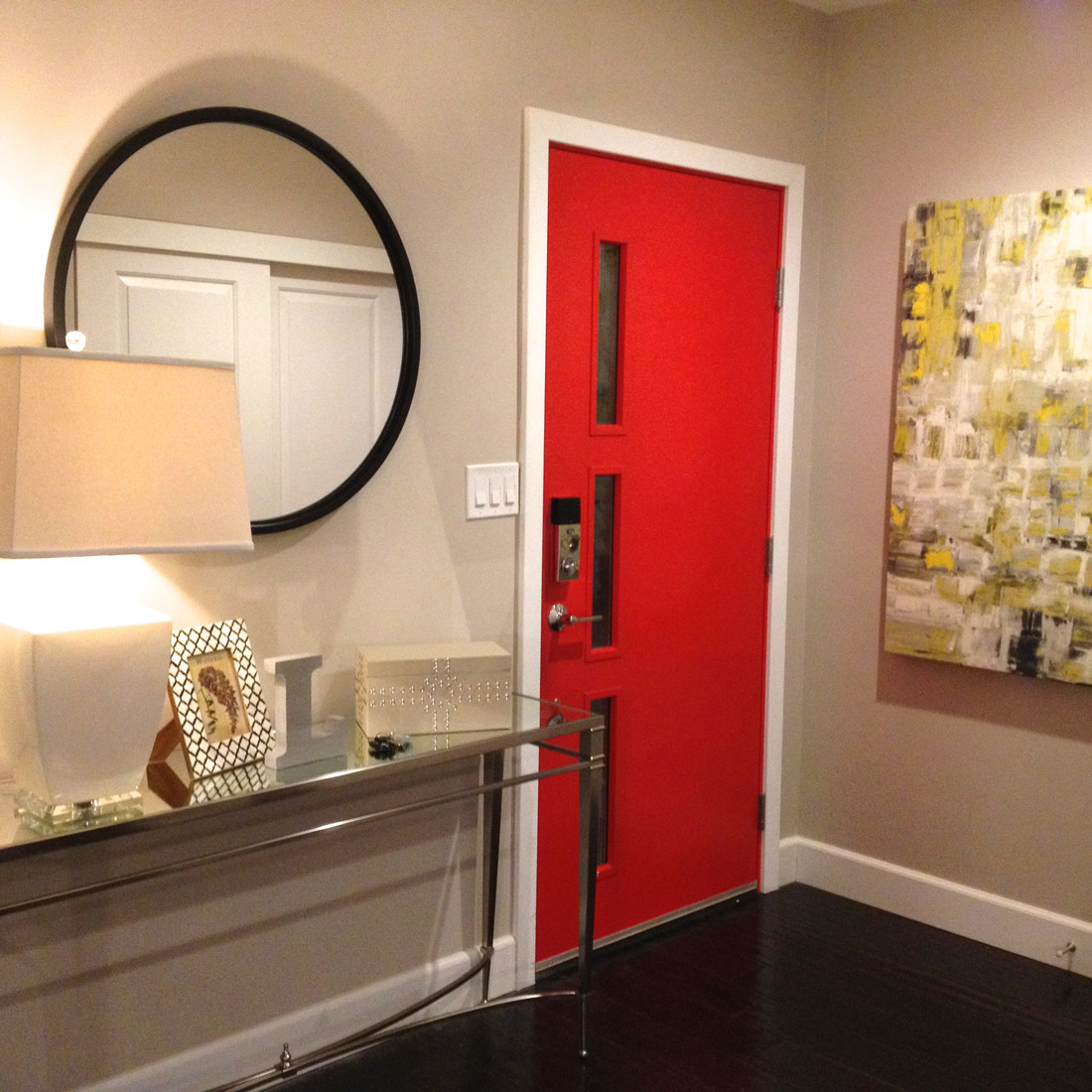 entryway with vibrant red door black circle mirror with console table and large lamp graphic yellow and grey modern artwork design by sara bates interior design