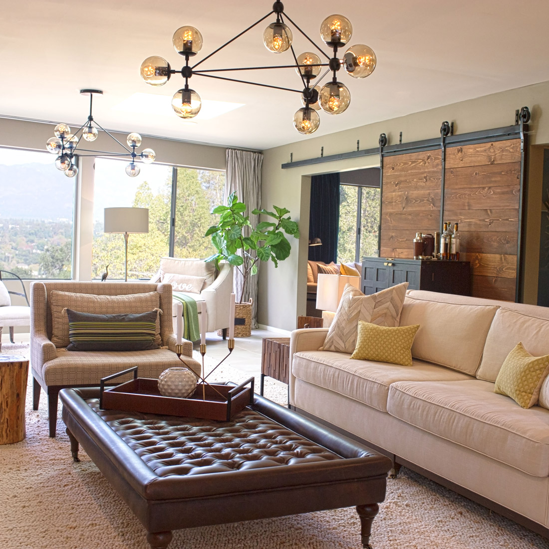 Living room with linen sofa and geometric upholstered chair and tufted leather ottoman with modern globe pendant light a large barn door divides the living room from the family room design by sara bates interior design