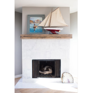 marble fireplace surround with a rustic wood mantel and beach side decor sail boat and art with light oak hardwood flooring design by sara bates interior design