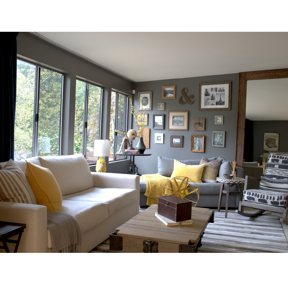 family room tv watching with linen sofa and upholstered rocking chair and very large mirror to expand the space dark grey walls create a cozy environment and a nice gallery wall to display pictures rustic wood coffee table and cow hide rug with yellow and grey colors design by sara bates interior design