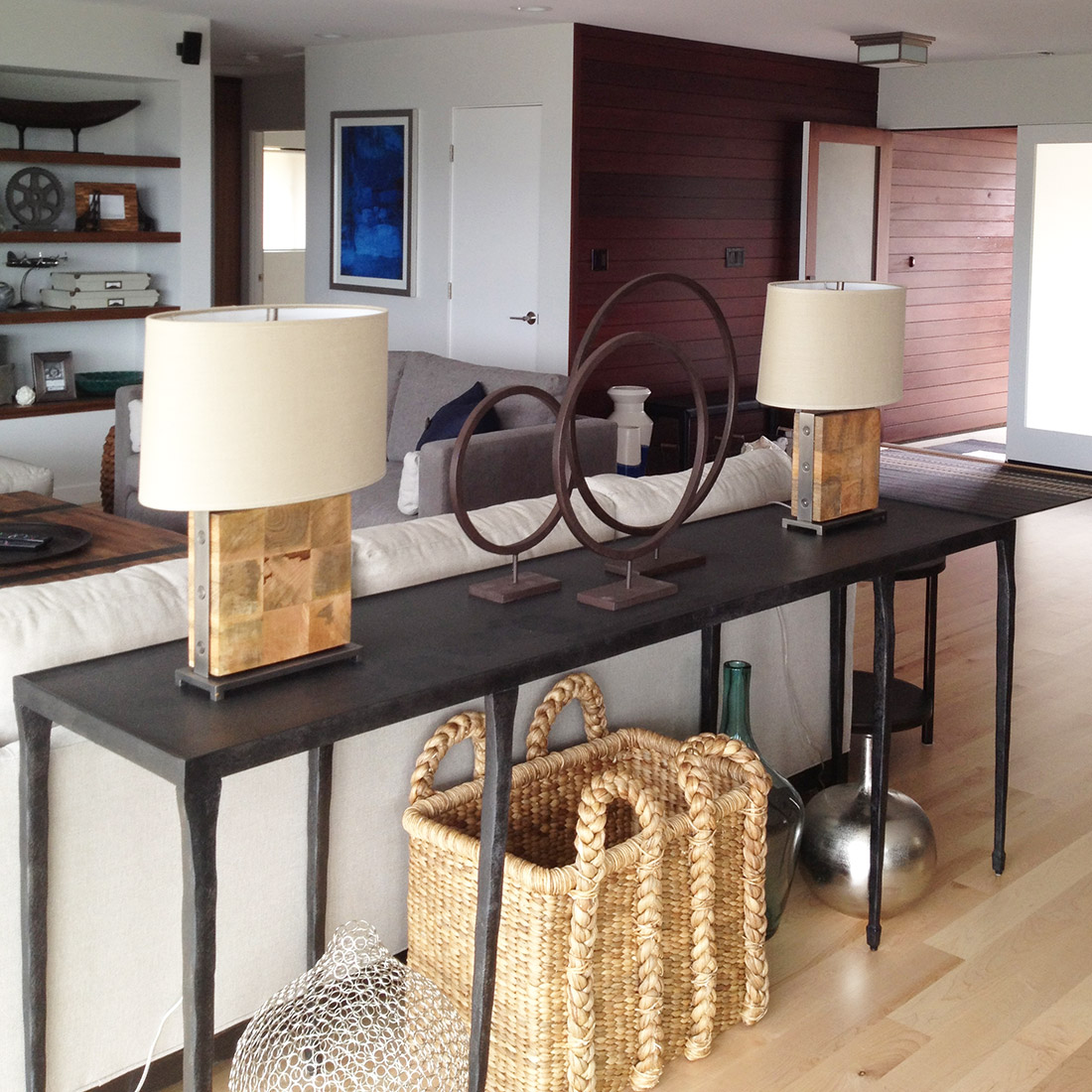 modern living room with a sofa table in black metal and wood base lamps with decor display basket and vases and ring objects design by sara bates interior design