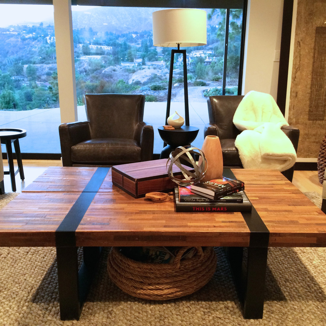 living room with canyon views and reclaimed wood coffee table over wool rug and seating group of dark grey leather chairs design by sara bates interior design