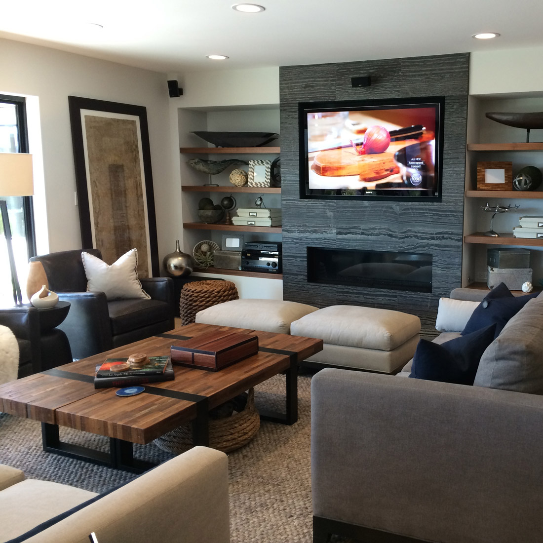 living room with zebrano marble stripe tiles surrounding tv and fireplace with built in floating walnut shelves reclaimed wood coffee table and chunky wool rug anchor the two sofas and dark grey leather chairs design by sara bates interior design