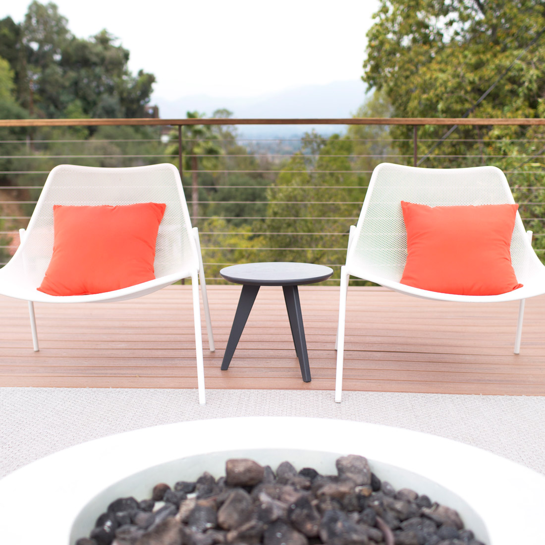 roof top patio with modern mesh white chairs and orange pillows in front of a gas fireplace with concrete surround design by sara bates interior design