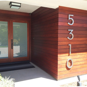 modern large address numbers and ipe wood paneling lead you to the modern french door entry with glass inserts and concrete flooring design by sara bates interior design