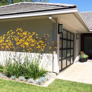 modern ranch home remodel with smooth grey stucco and modern metal and glass garage door and landscaping design by sara bates interior design