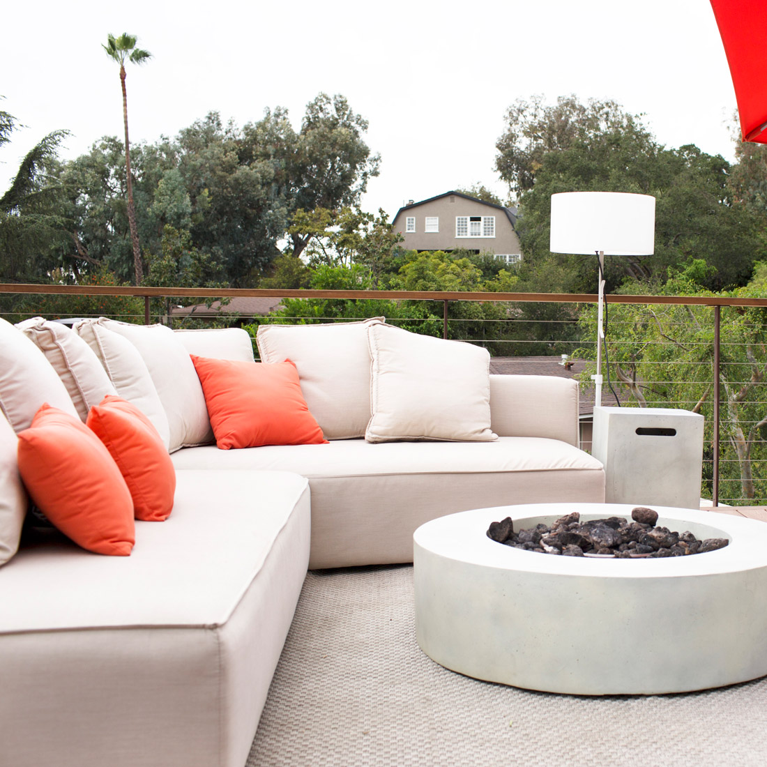 modern outdoor lounge sectional sofa with orange accents and floor lamp around a gas concrete fireplace on roof deck design by sara bates interior design
