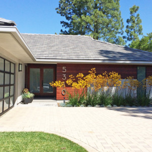 exterior remodel of ranch home with smooth grey stucco and ipe wood paneling and modern french doors with black metal and glass garage doors and modern landscaping design by sara bates interior design