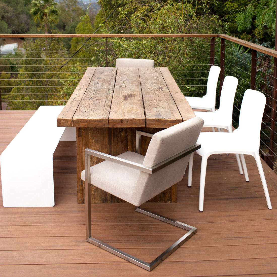 outdoor dining set with white plastic chairs and bench and metal frame upholstered chairs and rustic reclaimed wood dining table design by sara bates interior design