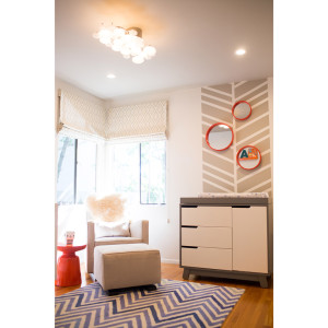 modern nursery with chevron wall detail and orange round mirrors and upholstered glider and ottoman with orange side table and blue zig zag rug design by sara bates interior design