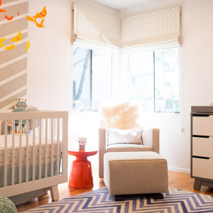 nursery with modern suede upholstered glider and ottoman with orange side table and white crib over a blue zig zag rug design by sara bates interior design