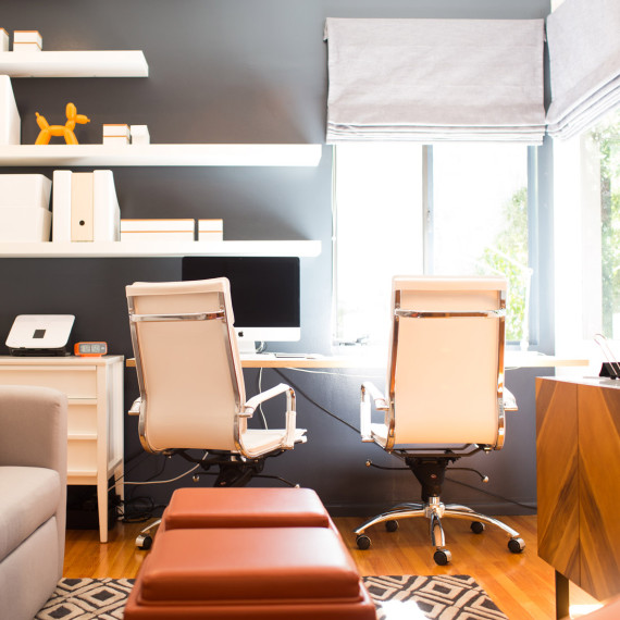 A collaborative work space office for the home with two leather white chairs and white desk with white floating shelves and dark wall for high contrast design by sara bates interior design