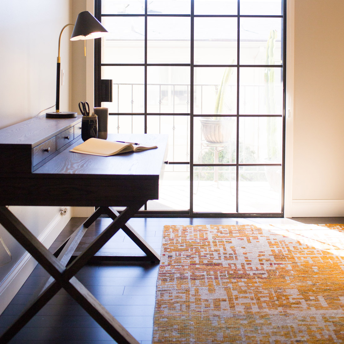 home office with wood writing desk and orange graphic rug design by sara bates interior design